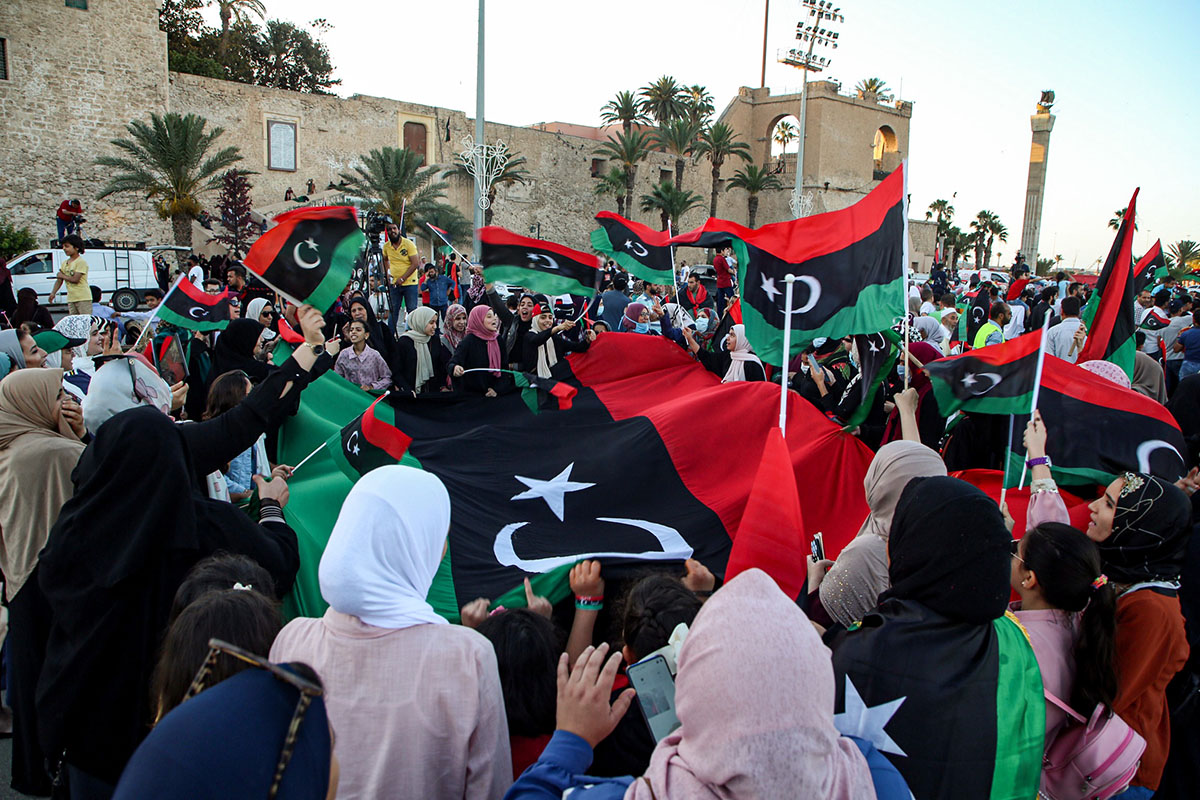 People celebrate with Libyan national flags, some clad in masks due to the COVID-19 coronavirus pandemic, in the capital Tripoli's Martyrs' Square on June 5, 2020, after fighters loyal to the UN-recognised Government of National Accord (GNA) captured the town of Tarhuna, about 65 kilometres southeast of the capital from rival forces loyal to strongman Khalifa Haftar. - The GNA said on June 5 that it was back in full control of Tarhouna, the last stronghold of the forces of eastern strongman Khalifa Haftar. The UN-recognised government had announced the day before that they were also in full control of the capital Tripoli and its surroundings. (Photo by - / AFP) (Photo by -/AFP via Getty Images)