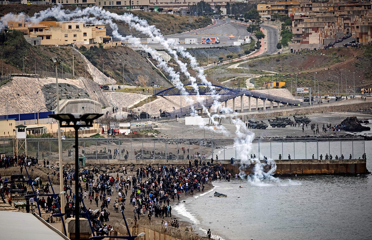 Spanish security forces launch tear gas canisters across a border fence as Moroccan migrants rally in the northern town of Fnideq to attempt crossing the border from Morocco to Spain's North African enclave of Ceuta on May 18, 2021. - At least 5,000 migrants, an unprecedented influx at a time of high tension between Madrid and Rabat, slipped into Ceuta on May 17, a record for a single day, Spanish authorities said. They reached the enclave by swimming or by walking at low tide from beaches a few kilometres to the south, some using inflatable swimming rings and rubber dinghies. (Photo by FADEL SENNA / AFP) (Photo by FADEL SENNA/AFP via Getty Images)